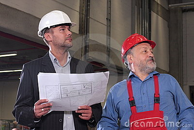 Two professionals with set of blueprints