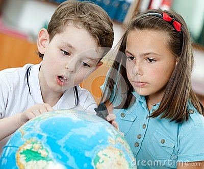 Two pupils look at the globe