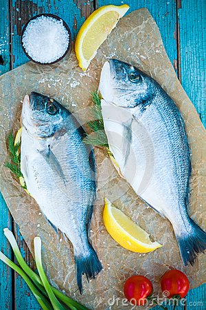 Free Two Raw Dorada Fishes With Lemon, Green Onions And Cherry Tomatoes Stock Photos - 42850863