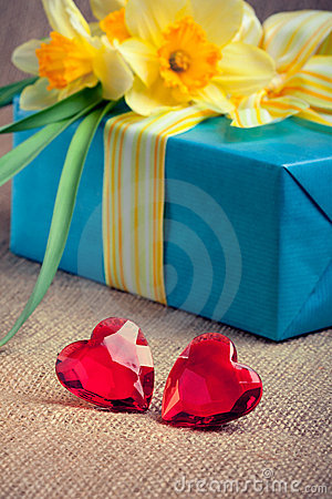 Two red glass hearts with a gift box and flowers