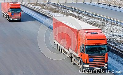 Two red tractor trailer trucks caravan convoy line