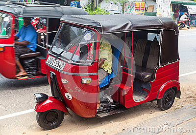 Two red tuk-tuk vehicles on street of Hikkaduwa Editorial Stock Photo