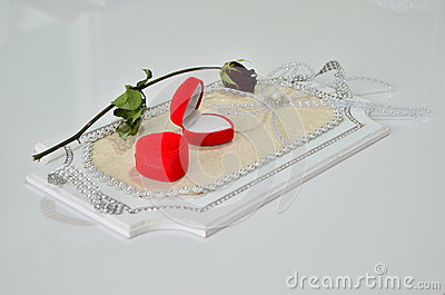 Two ring boxes and a rose on a tray.