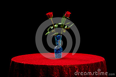 Two roses on a red lace table cloth