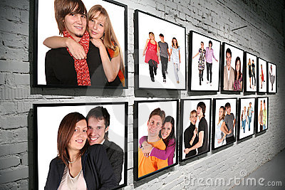 Two rows frames with people on brick white wall
