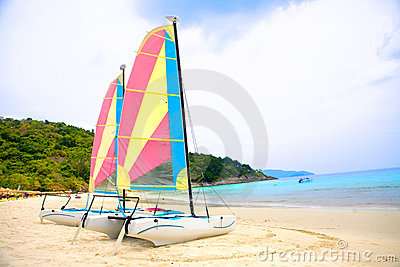 Two sailboats by a sandy beach