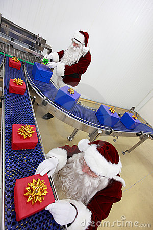 Two santa clauses working at production line