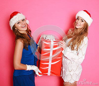Two santa girlfriends with a red gift in studio