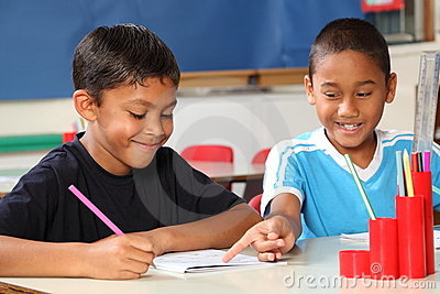 Two schoolboys helping each other learn in class d