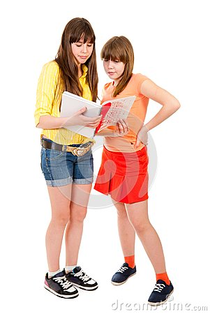 Two schoolgirls teenagers read something