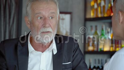 Two senior businessman drink beverage and discussion for congratulation with success in bar. Business elder man happy and fun drink beer in party with partner stock video