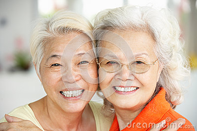 Two Senior Chinese Women Sitting At Home