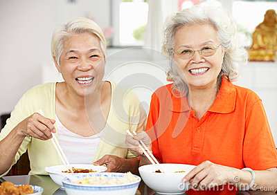 Two Senior Chinese Women Sitting At Home Eating