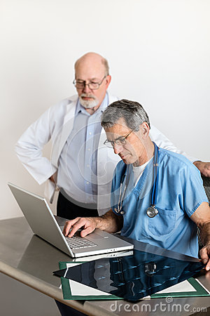 Two Senior Medical Doctors Discussing Patient s MRI Film Scans