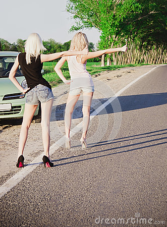 Two sexy girls standing near car and hitchhiking