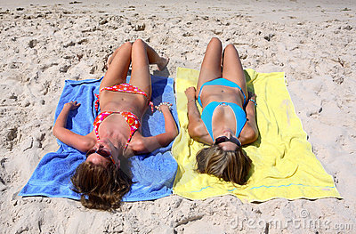 Two sexy young girls laying on a sunny beach on vacation or holi