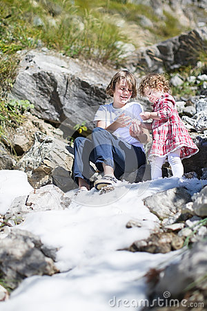 Two siblings playing with snow in mountains