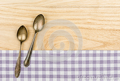 Two silver spoons on a purple checkered table cloth