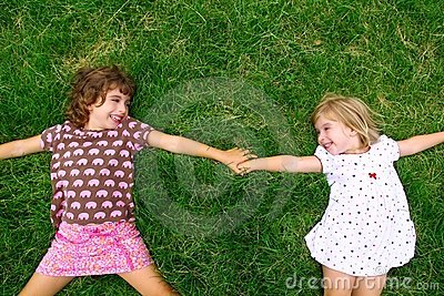 Two sister girls lying on meadow green grass