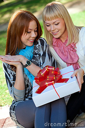 Two sisters with gift in the park