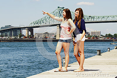 Two sisters interacting with bridge behind