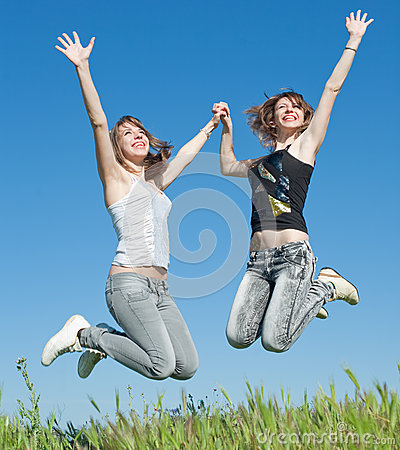 Two sisters in jeans jumping outdoors
