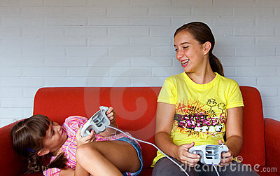 Two Sisters laughing, playing video games