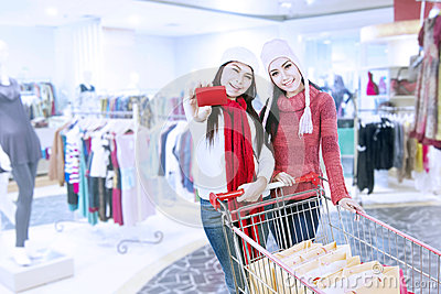 Two sisters shopping with gift card at mall