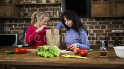 Two sisters unpacking shopping bag in the kitchen stock video