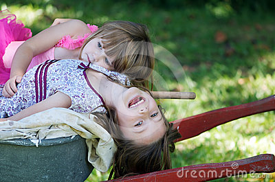 Two sisters on wheelbarrow