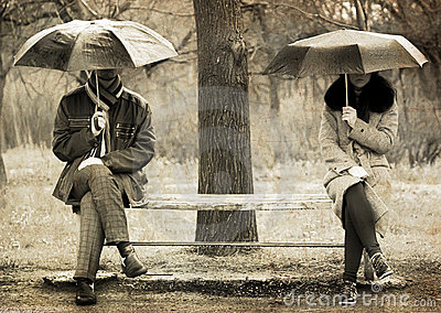 Two sitting at bench in rainy day.