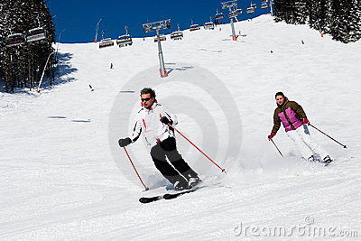 Two skiers downhill skiing