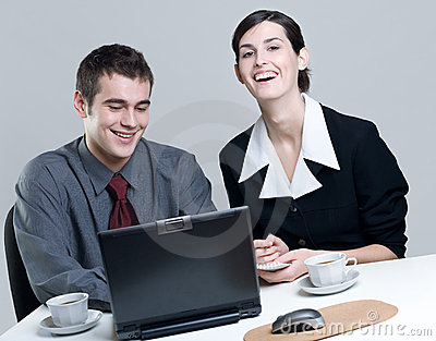Two smiling business people on laptop