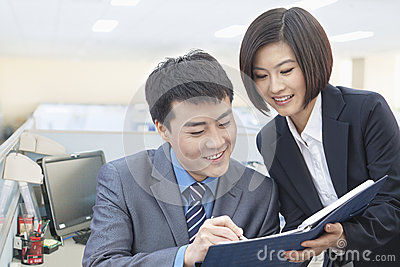 Two Smiling Business People Looking Down at Note Pad and Working Together