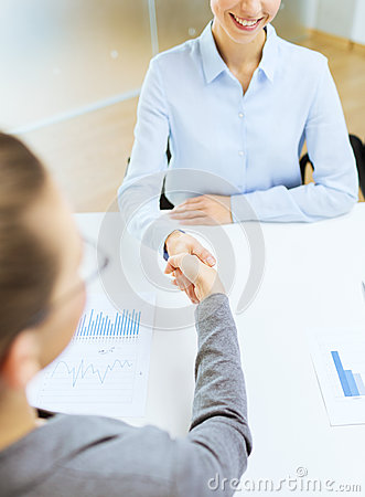Two smiling businesswoman shaking hands in office