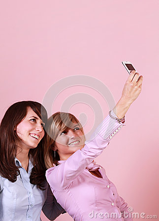 Two smiling friends using cell phone for a photo
