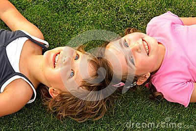 Two smiling girl lying on the grass
