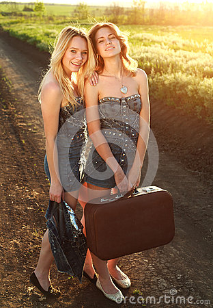 Two smiling girlfriend,with suitcase at countryside