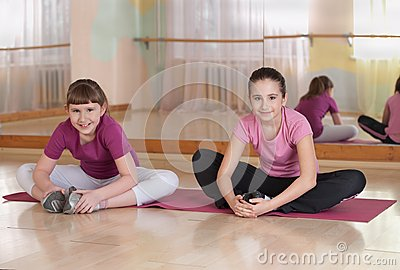Two smiling girls engaged in physical training.