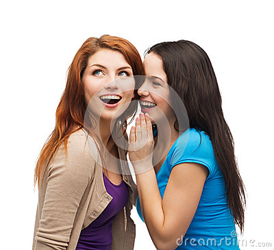 Two smiling girls whispering gossip