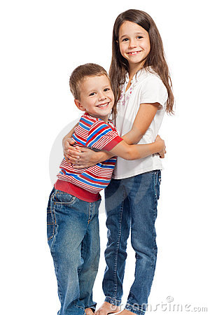 Two smiling little kids hugging each other