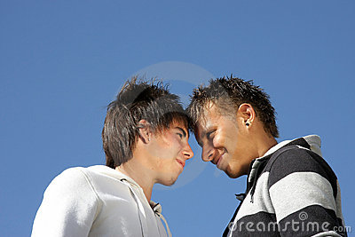 Two smiling teenagers standing head to head