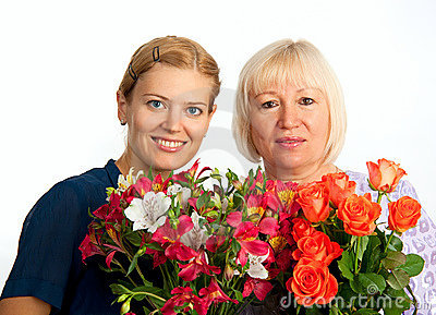 Two smiling women with flowers on white background