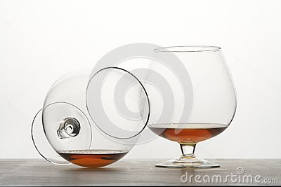 Two snifters of cognac on table.