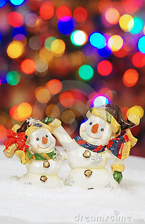 Two snowman with christmas lights in the background