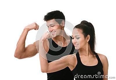 Two sportive people in black showing biceps