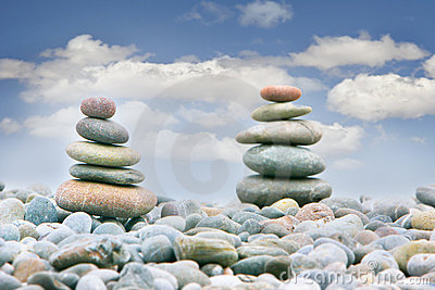 Two stacks of stones over sky background