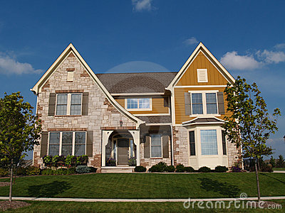 Two story stone, brick and board sided home.