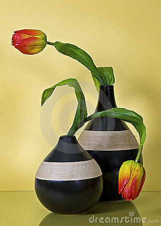 Two striped ceramic vases with flowers on yellow