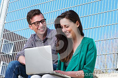 Two students working together on laptop outdoors
